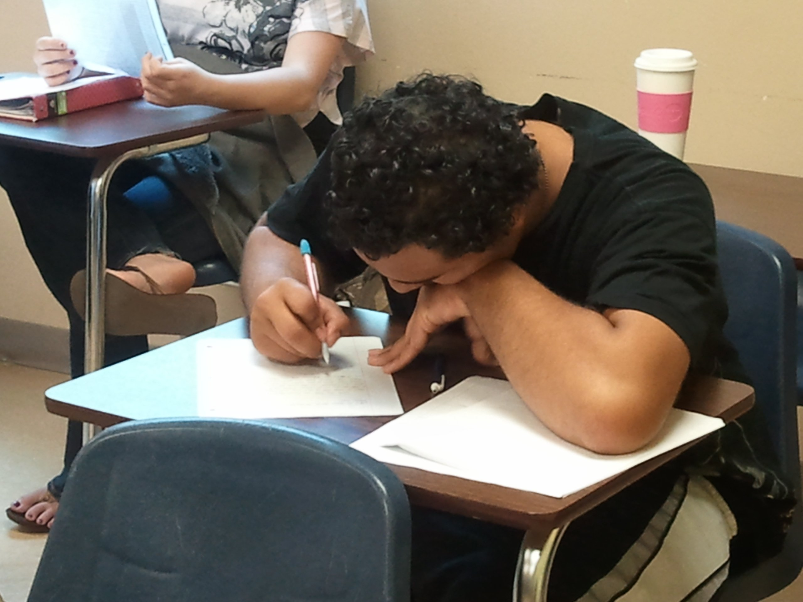 High school student writing at his desk
