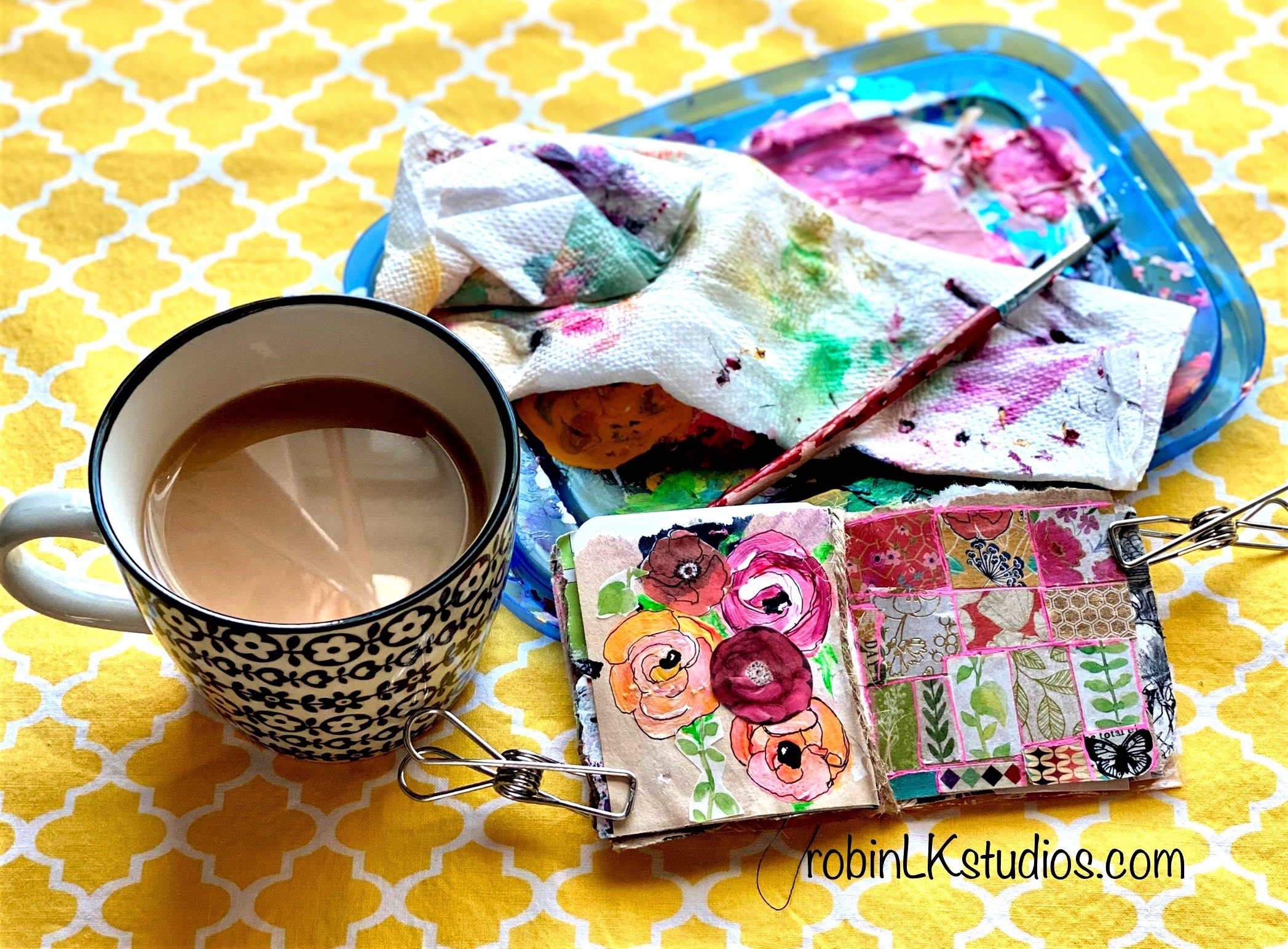 mini journal and coffee cup on a yellow tablecloth