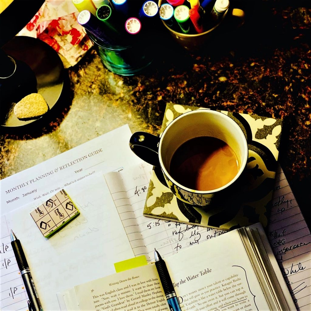 coffee cup with writing notebook, book, and pen